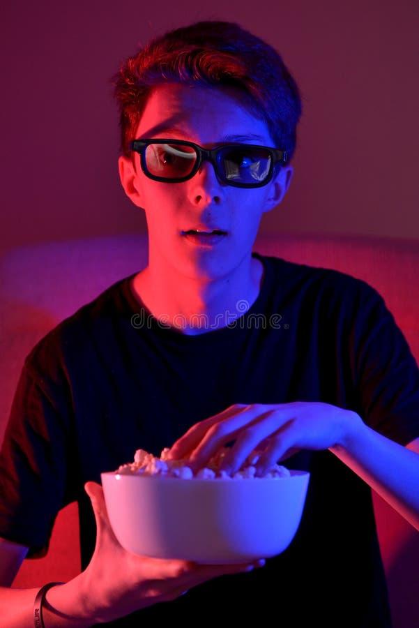 Sitzender und aufpassender Film des Jungen stockbilder