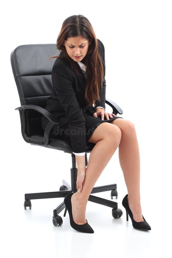Sitzender und leidender Fußschmerz der Geschäftsfrau lizenzfreie stockbilder
