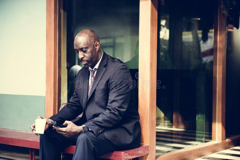 Sitzendes alleinarbeiten des Geschäftsmannes an Telefon stockbild