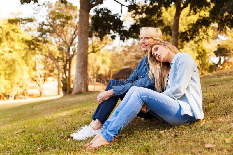 Sitzendes Gras der Muttertochter lizenzfreies stockfoto