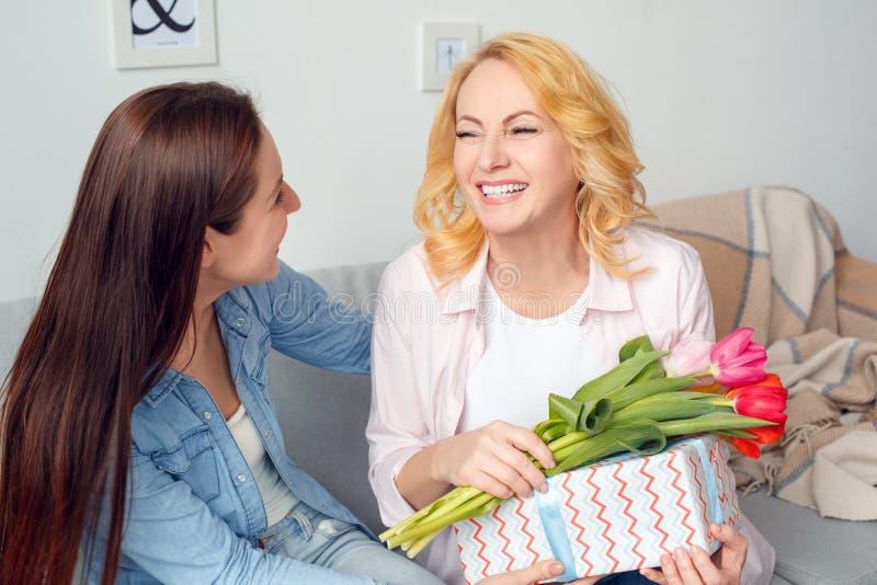 Sitzendes Holdinggeschenk und -tulpen der Mutter und der Tochter der Mutter der Feier zusammen zu Hause vom Tochterlachen froh lizenzfreie stockfotografie