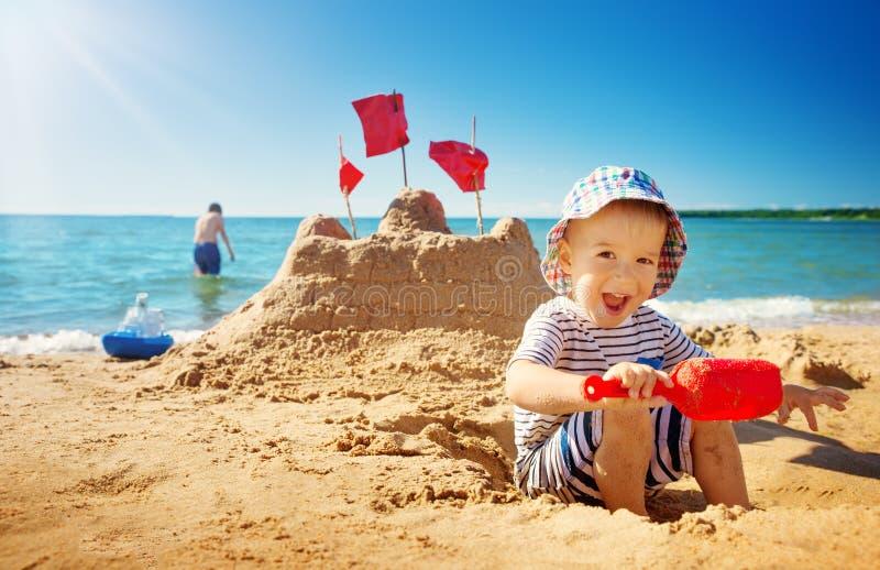 Sitzendes Lächeln des Jungen am Strand lizenzfreie stockfotografie