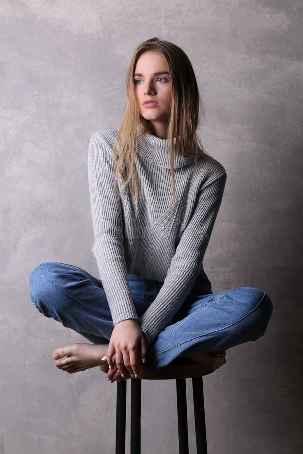 Sitzendes Mädchen in der Strickjacke mit den gekreuzten Beinen Grauer Hintergrund stockbilder