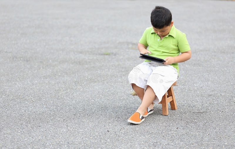 Sitzendes Spiel des Jungen eine Tablette stockbilder