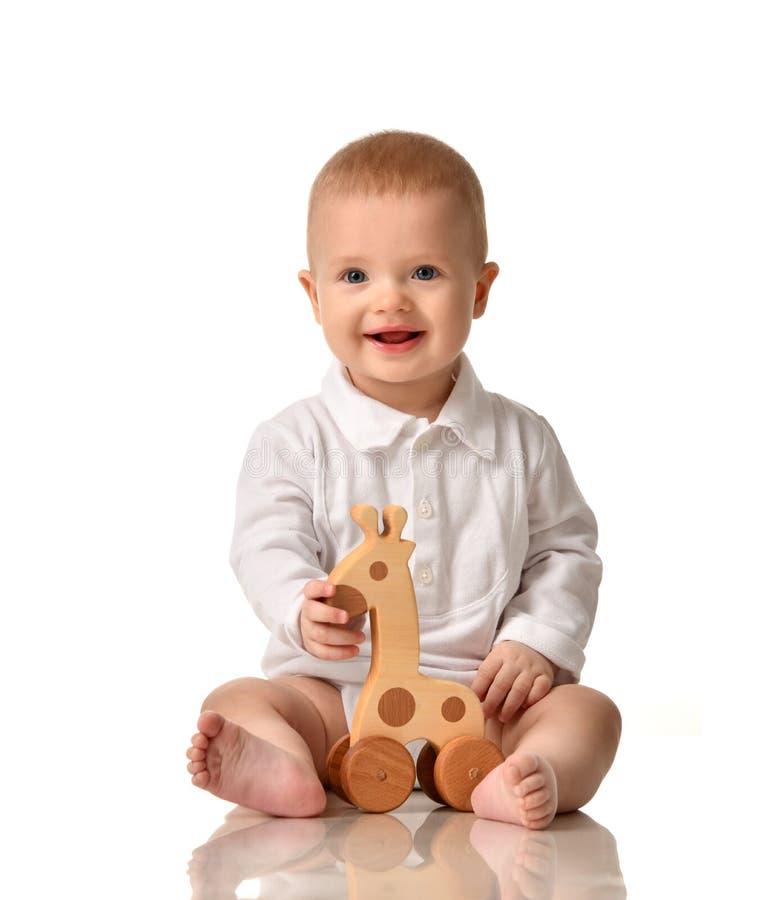 Sitzendes Spielen des Säuglingskinderbaby-Kleinkindes mit eco des hölzernen dem glücklichen Lächeln Giraffen-Spielzeugs lizenzfreie stockfotos