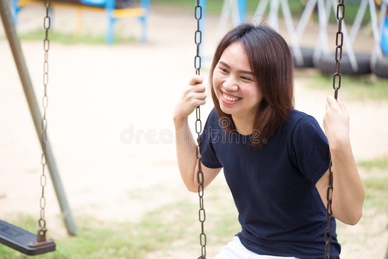 Sitzendes Spielschwingen des asiatischen gesunden jugendlich zufälligen Stofflächelns der Abnutzung lizenzfreie stockbilder