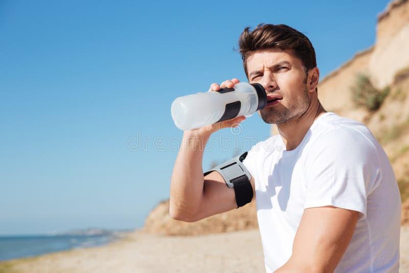 Sitzendes und Trinkwasser des Sportlers auf dem Strand stockbilder