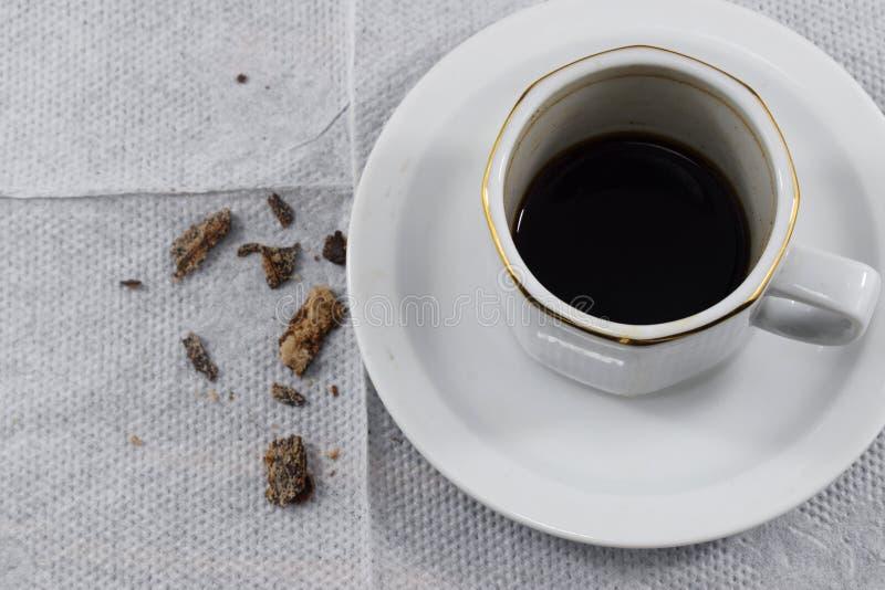 Sitzfrühstücksmorgen, übrig gebliebener Kaffee und Krumen lizenzfreie stockbilder