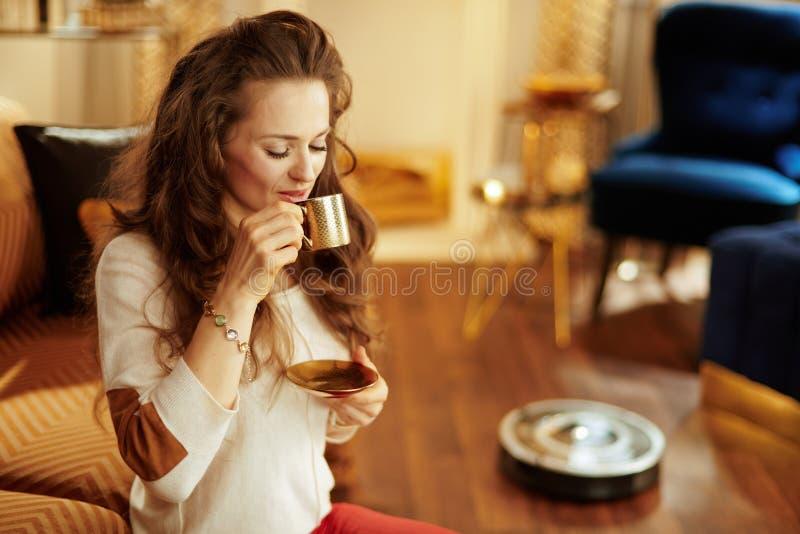 Sitzfrau, die Espresso während Roboterstaubsaugenboden isst stockfotos