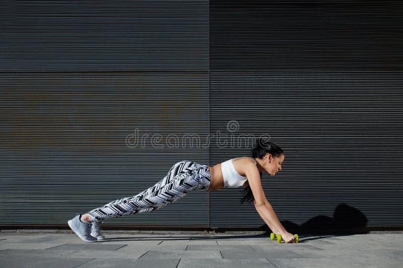Sitzfrau im Trainingsgang, der draußen StoßUPS auf schwarzem Hintergrund tut stockfotografie