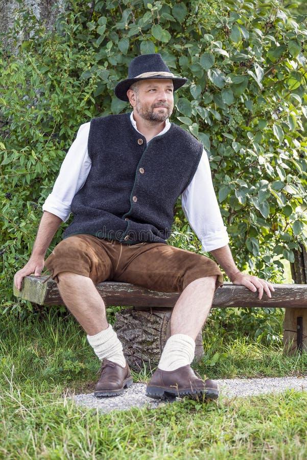 Sitzmann in den traditionellen bayerischen Kostümen und im schwarzen Hut lizenzfreies stockbild