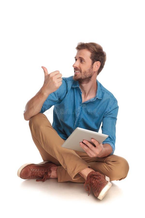 Sitzmann mit Tablette das okayzeichen zeigend oder machend stockbilder