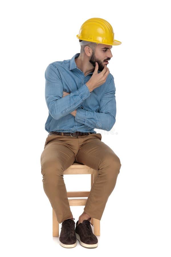 Sitzmodemann, der mit den gefalteten Armen beim Schauen vorsichtig denkt stockfoto