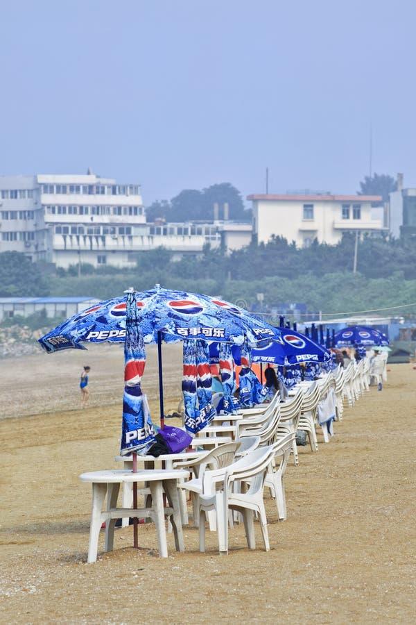 Sitzreihe mit Pepsi-Sonnenschirmen auf einem Strand, Yantai, China lizenzfreie stockbilder