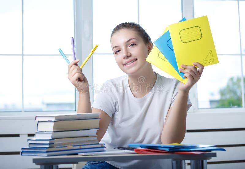 Sitzt jugendlich Studentin des netten Jugendlichen am Tisch mit Buh stockfotos