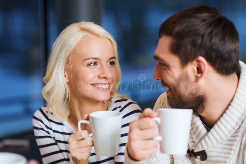 Sitzung des glücklichen Paars und trinkender Tee oder Kaffee stockbild