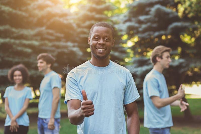 Sitzung von Jungen erbietet Team im Park freiwillig stockbild