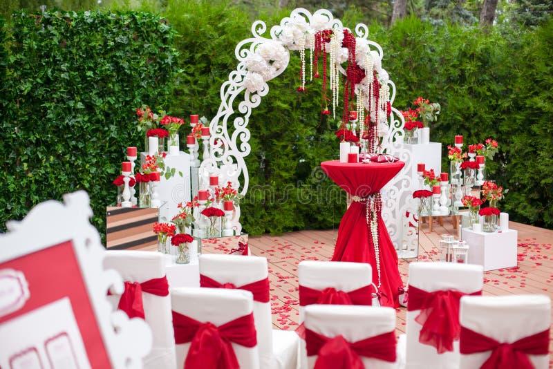 Sitzungsgäste an der Hochzeit - ein Bogen, Stühle, Blumen, Dekorationen stockbilder