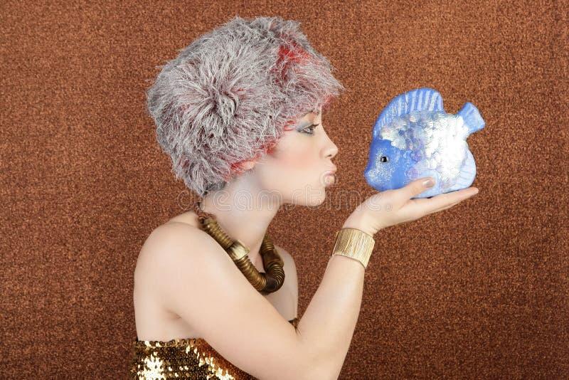 Siver y la mujer de la manera del oro besan pescados en el bronce foto de archivo
