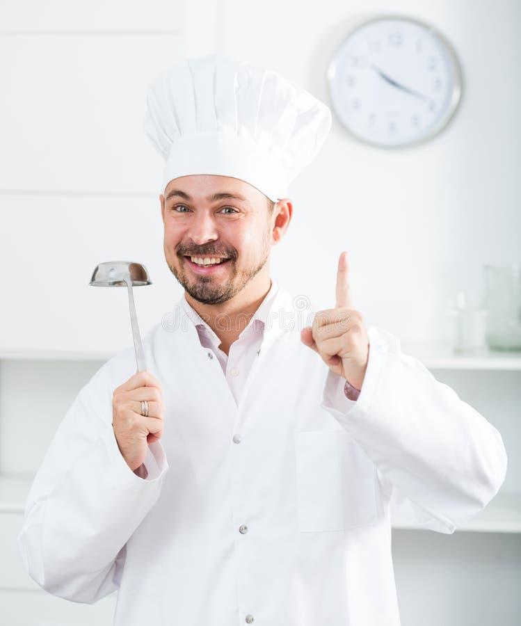 Siviera di minestra positiva della tenuta del cuoco dei giovani immagine stock libera da diritti