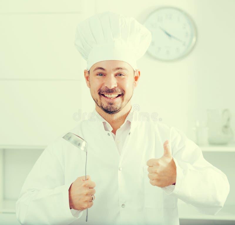 Siviera di minestra positiva della tenuta del cuoco dei giovani fotografia stock