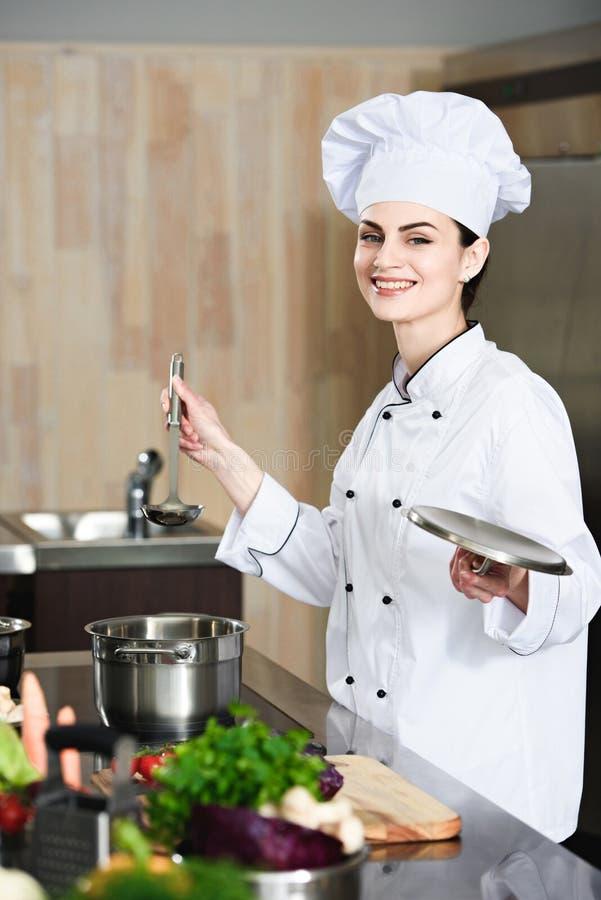 Siviera femminile professionale della tenuta del cuoco dalla stufa fotografia stock