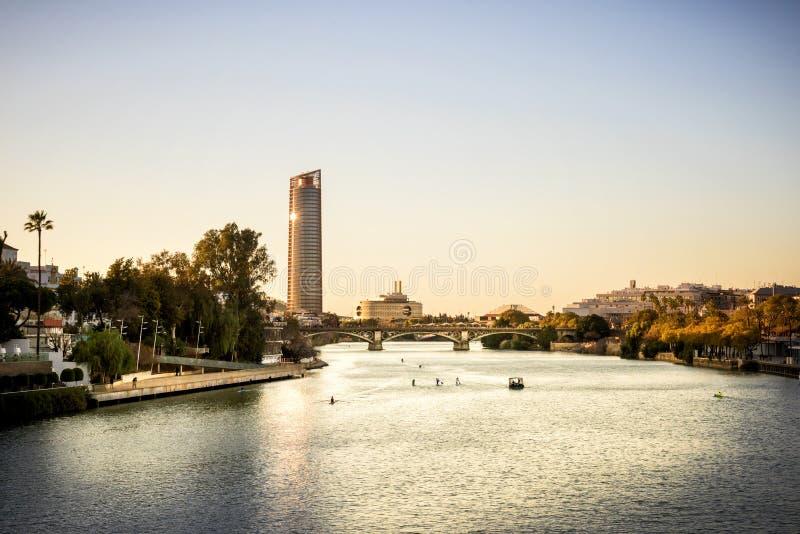 Siville - Siville塔Torre塞维利亚,安大路西亚,在河瓜达尔基维尔河的西班牙塞维利亚看法日落的 库存图片