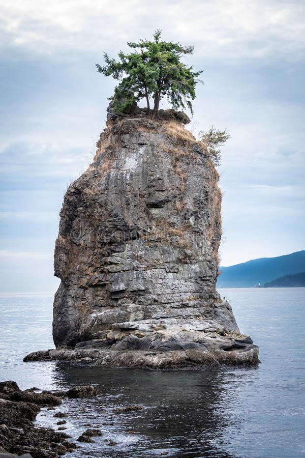 The Siwash Rock, also called the Nine Pin Rock. A famous sea stack by the coast at Stanley Park in Vancouver, British Columbia, Canada royalty free stock image