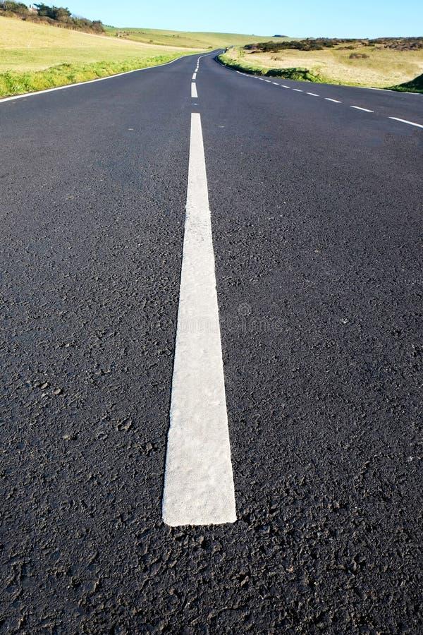 Siwieje asfaltowego kraju pas ruchu z silnymi białymi liniami w środku zdjęcie royalty free