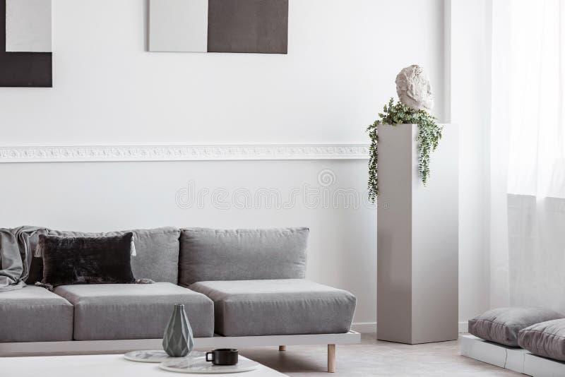 Siwieje betonową kolumnę z głową i zielenieje kwiatu w monochromatic żywym izbowym wnętrzu fotografia stock