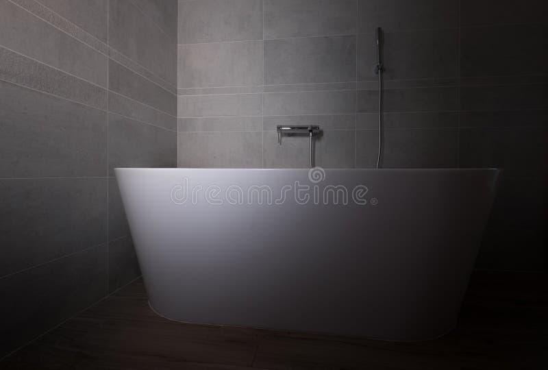 Siwieje kamienną kafelkową nowożytną łazienkę z białą wanny niskiego światła fotografią obrazy royalty free