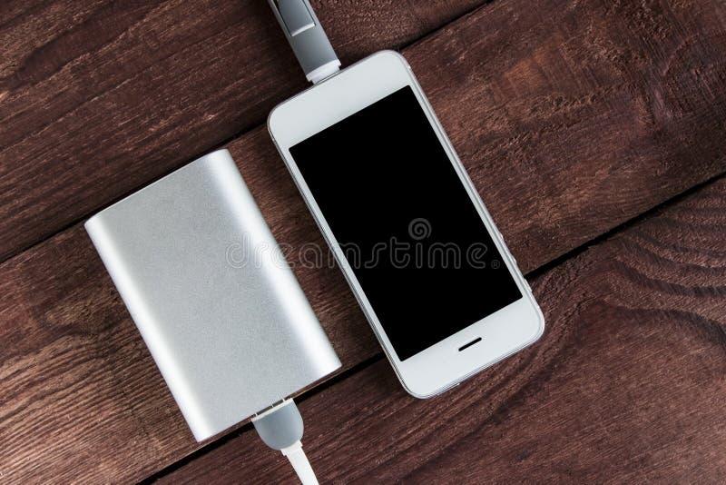 Siwieje telefon i zasila banka łączącego sznurem na drewnianym biurku zdjęcia royalty free