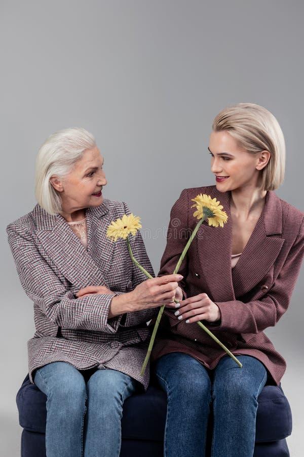 Siwowłosa starsza dama proponuje jej córka kwiatu zdjęcie royalty free
