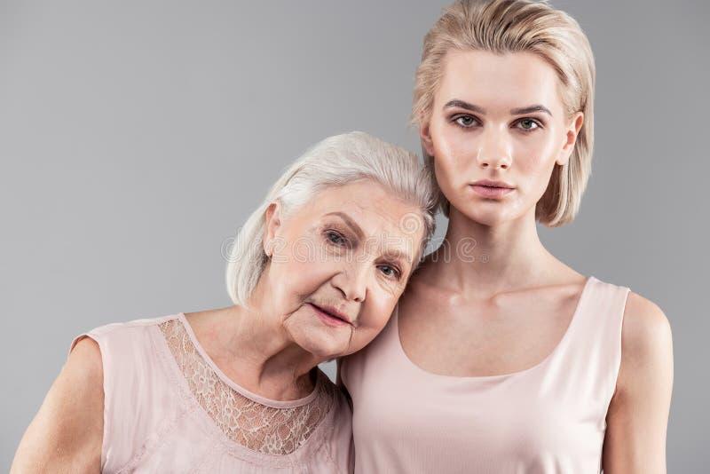 Siwowłosy żeński emeryt stawia jej głowę na malutkim ramieniu zdjęcia stock