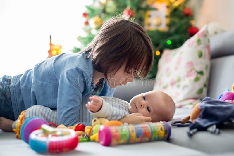 Six années de garçon préscolaire, jouant à la maison avec du son Ba nouveau-né photo stock