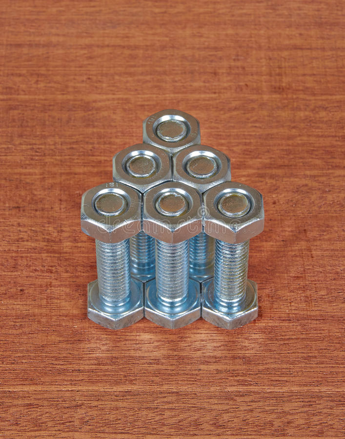 Six bolts with nuts. On a wooden plane stock photo