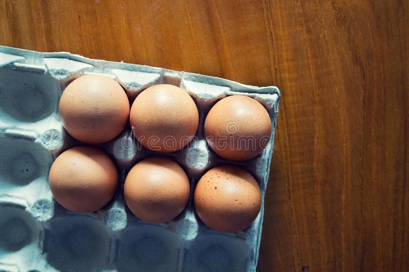 Six brown raw hen eggs on gray tray lying on wooden table royalty free stock photography