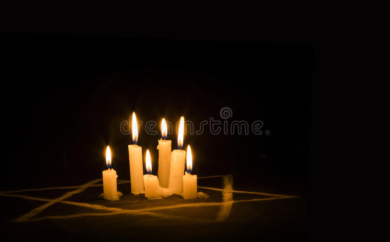 Six burning candles and the Star of David against a black background, text Yom Hashoah, We will never forget, the Jewish royalty free stock images