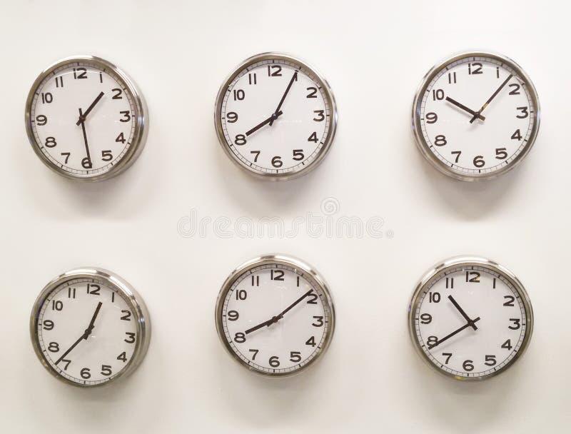 Six clocks on white wall royalty free stock photo