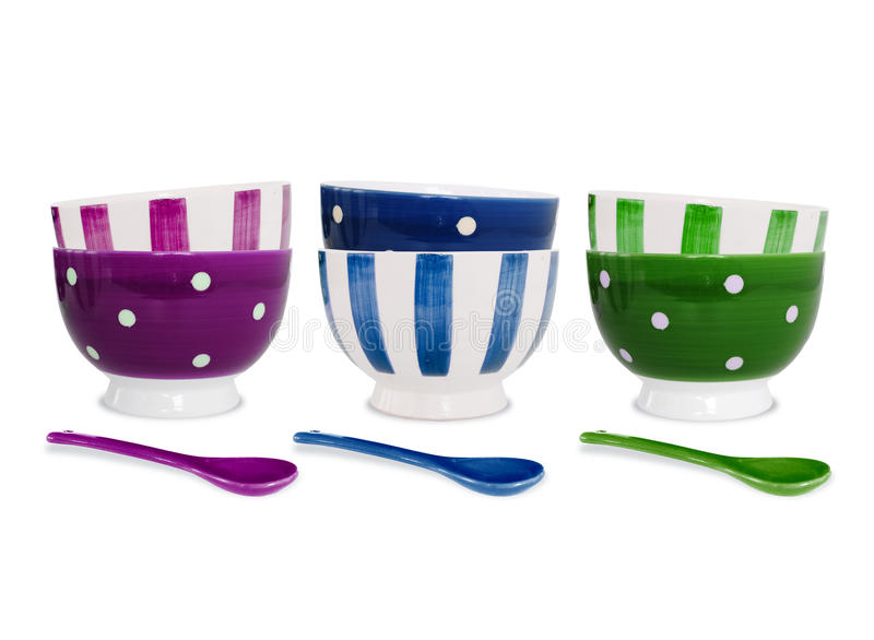 Six colorful bowls and spoons on white background stock image