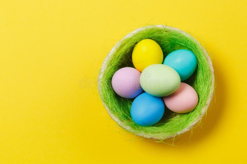 Six colorful pastel monophonic painted Easter eggs in basket with green grass isolated on yellow background. Happy stock image