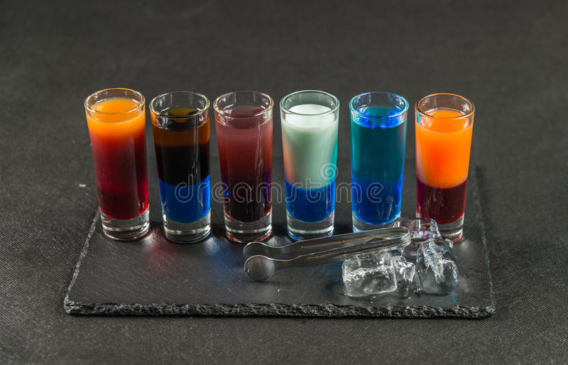 Six different colored shot drinks, lined up on a black stone plate, ice cubes and ice tongs royalty free stock photography