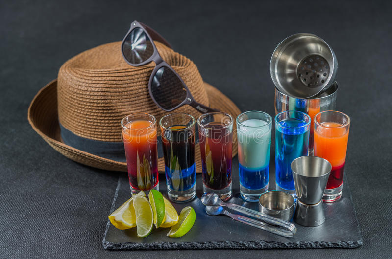 six different colored shot drinks, lined up on a black stone plate, ice cubes in shaker and ice tongs, lemon and lime, brown stock photos