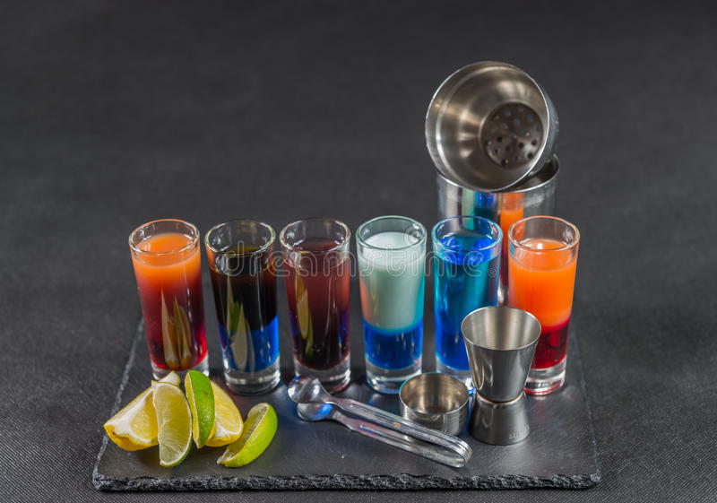six different colored shot drinks, lined up on a black stone plate, ice cubes in shaker and ice tongs, lemon and lime royalty free stock image
