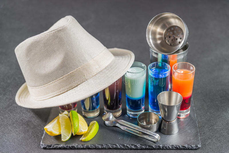six different colored shot drinks, lined up on a black stone plate, ice cubes in shaker and ice tongs, lemon and lime, white hat royalty free stock photography