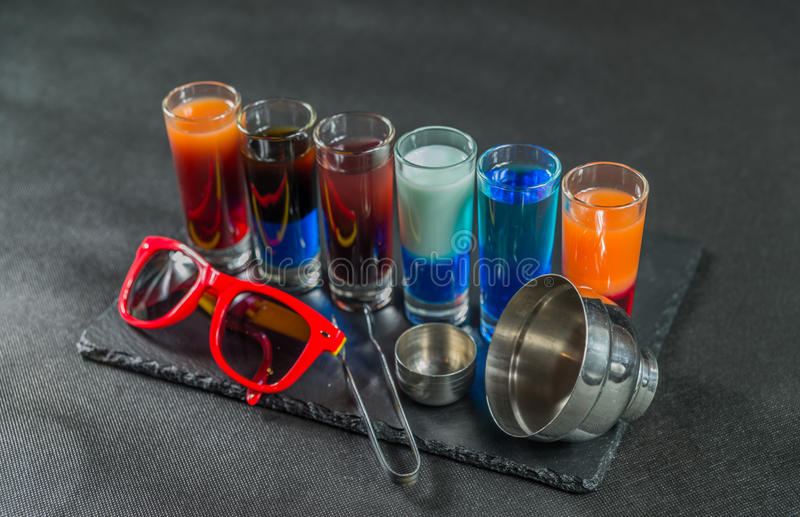 six different colored shot drinks, lined up on a black stone plate, ice cubes in shaker and ice tongs royalty free stock images