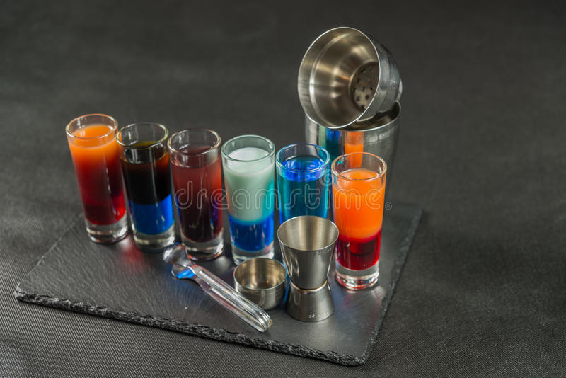 six different colored shot drinks, lined up on a black stone plate, ice cubes in shaker and ice tongs royalty free stock image
