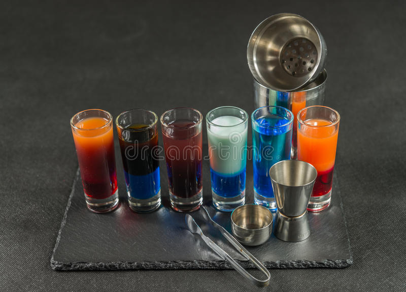 six different colored shot drinks, lined up on a black stone plate, ice cubes in shaker and ice tongs stock image