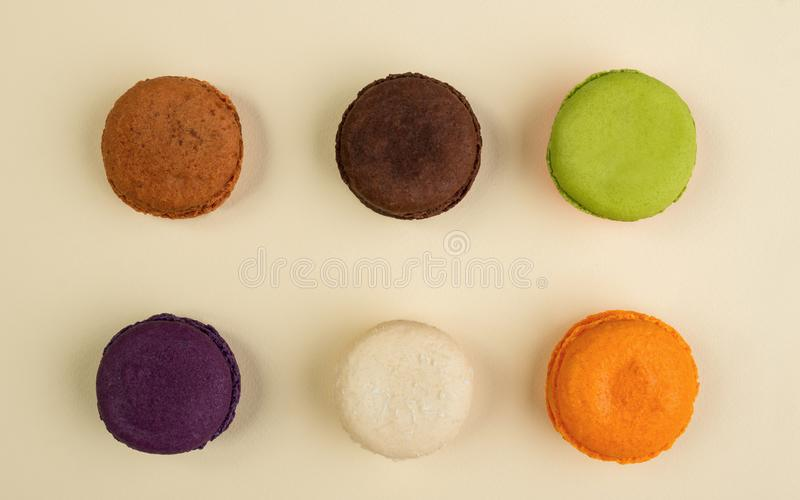 Six different Macarons flavors on beige background royalty free stock image