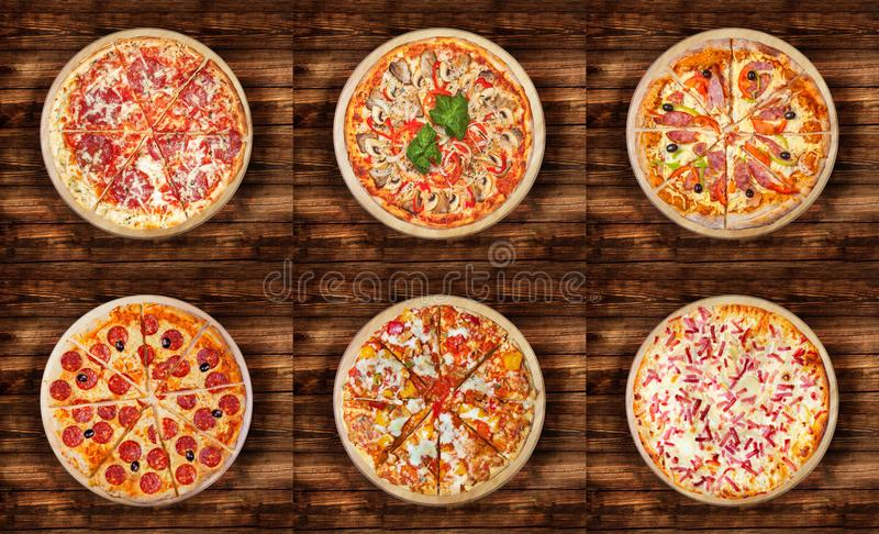 Six different pizza set for menu on the wooden table. Italian food traditional cuisine. Meat pizzas with salami, seafood, ham, p. Epperoni, barbecue and flaming royalty free stock photo